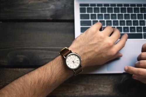 Homme qui regarde sa montre poignet ordinateur portable